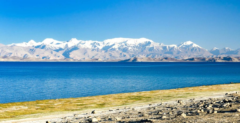 Karakul lake by the Pamir highway. View on the lake and Peak Lenin near Karakul village in the Pamirs, Tajikistan, Central Asia.