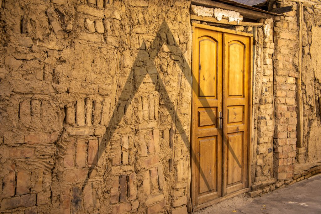 Brick clay wall in old town of Tashkent and a wooden door