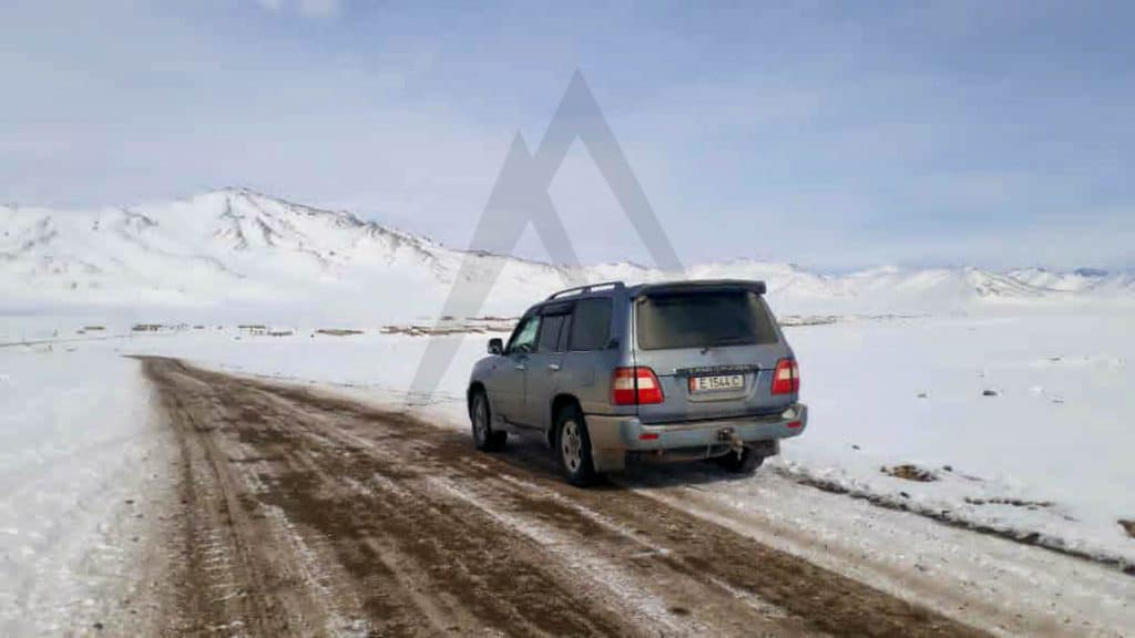 Car driving a snowy road in Pamir